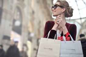 woman holding two white and beige shopping paper bags in building